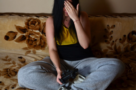 affliction: The girl sitting on the couch and show facepalm sign, playing on the game console. Young brunette is upset by the poor game result in the video game