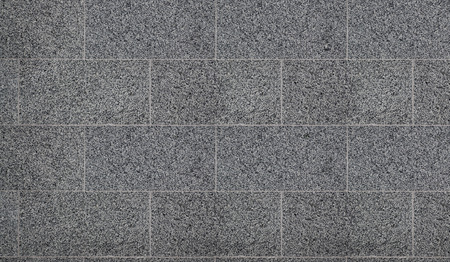 The texture of solid granite tiles. Hard and slippery gray granite surface with a relief discharge when exposed to sunlight