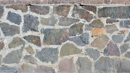 bedraggled: Stone wall background - building feature. Texture of thick and strong wall of rough stones of various shapes and sizes