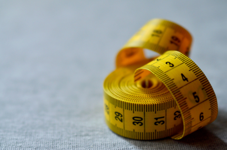 The measuring tape of yellow color with numerical indicators in the form of centimeters or inches lies on a gray knitted fabric. Background image about sewing sportswear for people, who slimming Stock Photo