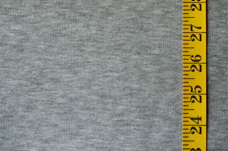 Yellow measuring tape with numerical indicators in the form of centimeters or inches lies on a gray knitted fabric. Concept industry associated with sewing sportswear for specific body sizes