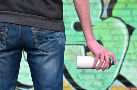 Rear view of the body of a young guy in blue dirty jeans and a gray sweater with a used paint spray in his hand against the background of an old brick wall painted in graffiti drawings Standard-Bild