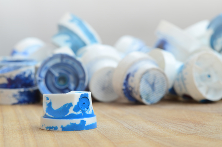 Several plastic nozzles from a paint sprayer that lie on a wooden surface against a gray wall background. The caps are smeared in blue paint. The concept of street art and graffiti Stock Photo