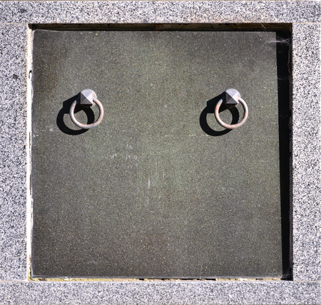 The front part of the granite crypt with metal ring handles in the cemetery