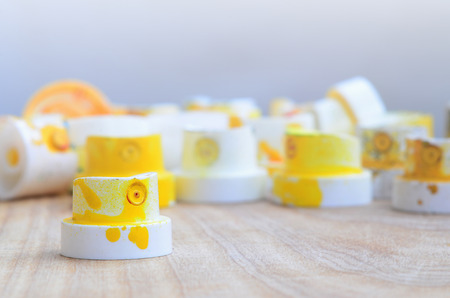 Several plastic nozzles from a paint sprayer that lie on a wooden surface against a gray wall background. The caps are smeared in yellow paint. The concept of street art and graffiti