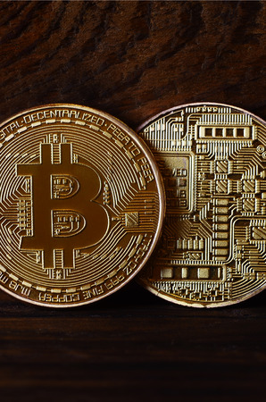 Two new golden physical bitcoins lies on dark wooden backgound, close up. High resolution photo. Cryptocurrency mining concept