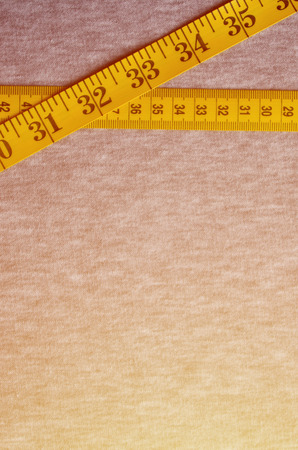 The measuring tape of yellow color with numerical indicators in the form of centimeters or inches lies on a gray knitted fabric. Background concept for sewing clothes for specific body sizes