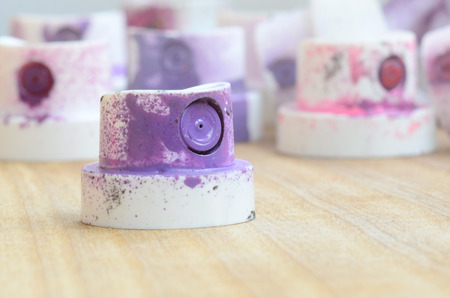 Several plastic nozzles from a paint sprayer that lie on a wooden surface against a gray wall background. The caps are smeared in violet paint. The concept of street art and graffiti