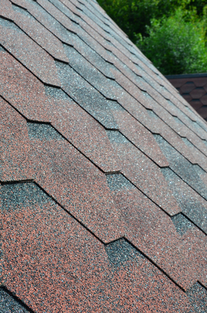 The texture of the roof with bituminous coating. Rough bituminous mosaic of red and brown flowers. Waterproof roofing