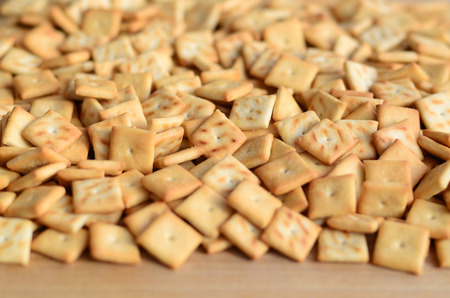 Background texture of small edible squares baked from dough and sprinkled with salt. A lot of salt cracker