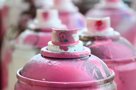 A lot of dirty and used aerosol cans of bright pink paint. Macro photograph with shallow depth of field. Selective focus on the spray nozzle Stock Photo