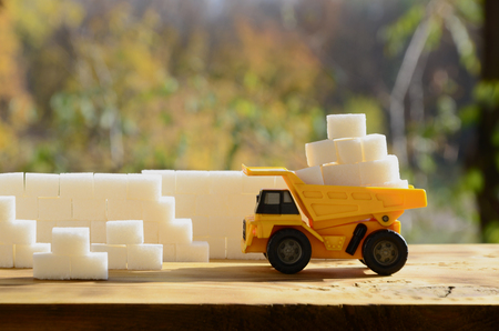 A small yellow toy truck is loaded with white sugar cubes near the sugar wall. A car on a wooden surface against a background of autumn forest. Extraction and transportation of sugar Stock Photo