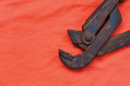 Adjustable wrench against the background of an orange signal worker shirt. Still life associated with repair, railway or plumbing works