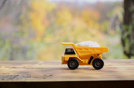 A small yellow toy truck is loaded with a stone of white salt. A car on a wooden surface against a background of autumn forest. Extraction and transportation of salt