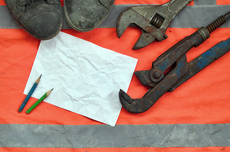 Adjustable wrenches with old boots and a sheet of paper with two pencils. Still life associated with repair, railway or plumbing works Stock fotó