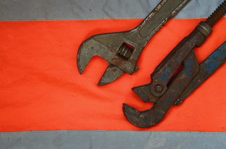 Adjustable and pipe wrenches against the background of an orange signal worker shirt. Still life associated with repair, railway or plumbing works Stock Photo