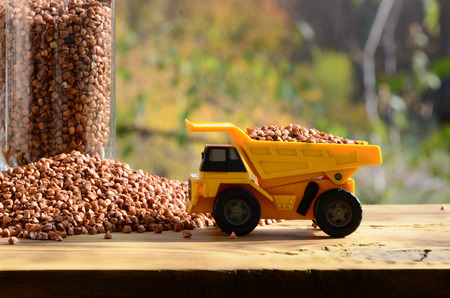 A small yellow toy truck is loaded with brown grains of buckwheat around the buckwheat pile and a glass of croup. A car on a wooden surface against a background of autumn forest. Buckwheat delivery Stock Photo