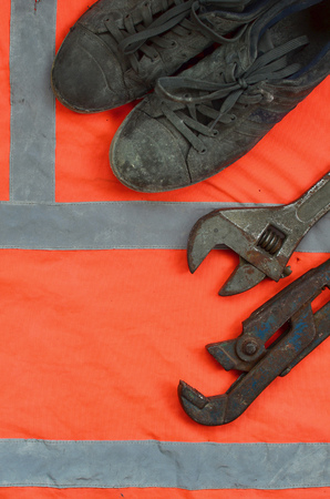 Adjustable wrenches and old boots lies on an orange signal worker shirt. Still life associated with repair, railway or plumbing works