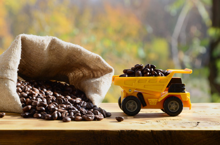 A small yellow toy truck is loaded with brown coffee beans around a full bag of grains. A car on a wooden surface against a background of autumn forest. Extraction and transportation of coffee Stock Photo