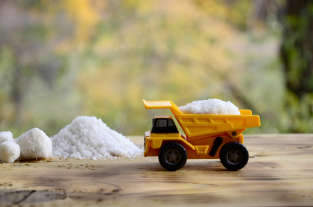 A small yellow toy truck is loaded with a stone of white salt next to a pile of salt. A car on a wooden surface against a background of autumn forest. Extraction and transportation of salt Stock Photo