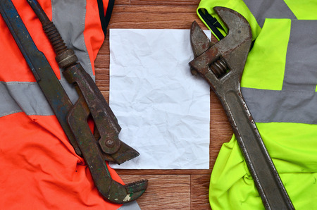 Adjustable wrenches and paper lies of an orange and green signal worker shirts. Still life associated with repair, railway or plumbing works Stock Photo