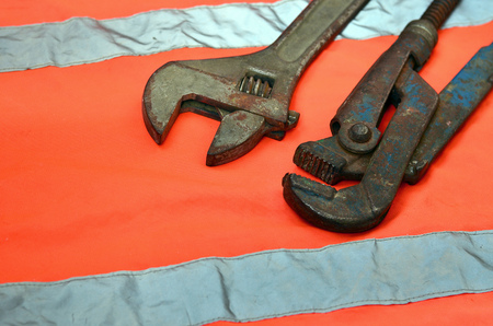 Adjustable and pipe wrenches against the background of an orange signal worker shirt. Still life associated with repair, railway or plumbing works Zdjęcie Seryjne