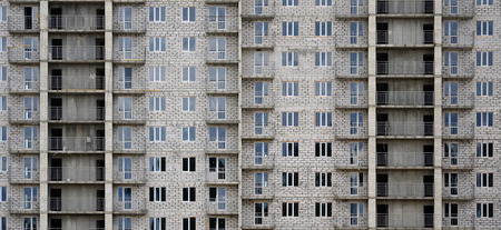 Textured pattern of a russian whitestone residential house building wall with many windows and balcony under construction