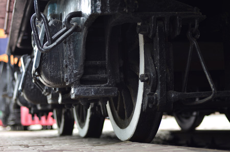 Wheels of a Russian modern locomotive, view from side. Transportation industry concept. Heavy wheels and mechanism under the electro train 写真素材