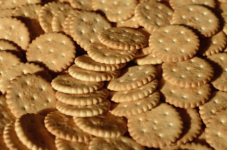 Closeup of salted crackers. Background image of classic salty cracker on a brown wooden table