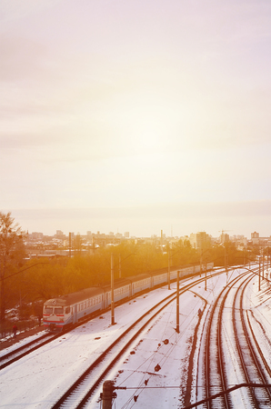 Winter landscape with a railway train on a railway surrounded by a city panorama with lots of houses and buildings against a cloudy sky background