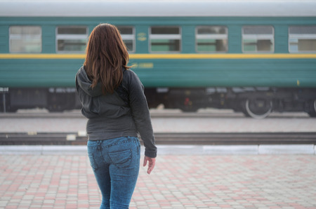 A young red-haired girl is standing on the railway platform and watching the departing train. The woman was late for her train. Back view