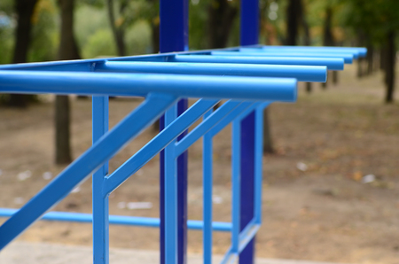 Blue metal pipes and cross-bars against a street sports field for training in athletics. Outdoor athletic gym equipment. Macro photo with selective focus and extremely blurred background
