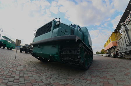 Photo of a Russian green armored car on a caterpillar track among the railway trains. Strong distortion from the fisheye lens Editorial