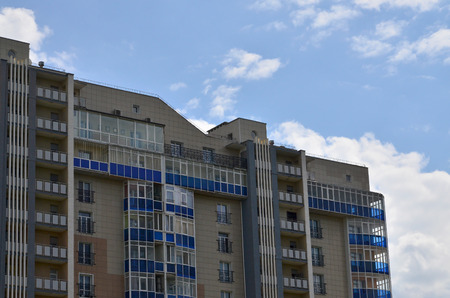 New or recently completed multi-storey residential building with windows and balconies. Russian type of house building