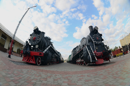 Photo of old black steam locomotives of the Soviet Union. Strong distortion from the fisheye lens