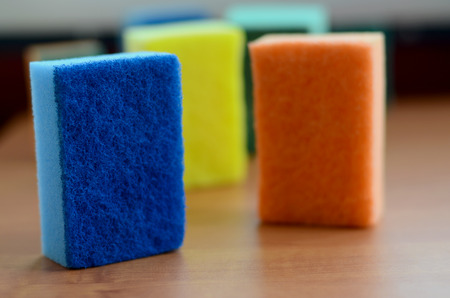 A few kitchen sponges lie on a wooden kitchen countertop. Colorful objects for washing dishes and cleaning in the house are ready for use
