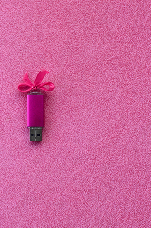 Brilliant pink usb flash memory card with a pink bow lies on a blanket of soft and furry light pink fleece fabric. Classic female gift design for a memory card Banque d'images