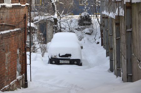 KHARKOV, UKRAINE - DECEMBER 4, 2016: A parked car under a thick layer of snow. Consequences of a strong and unexpected snowfall in Ukraine
