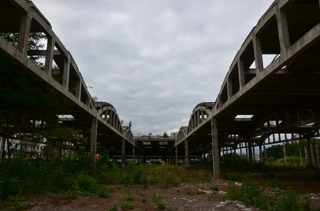 Landscape image of an abandoned industrial hangar with a damaged roof. Photo on wide-angle lens
