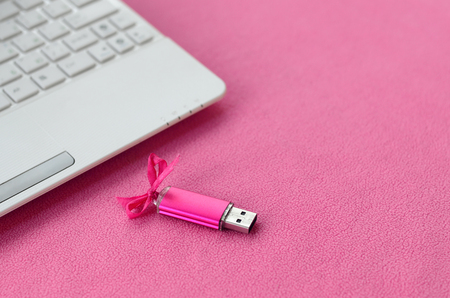 Brilliant pink usb flash memory card with a pink bow lies on a blanket of soft and furry light pink fleece fabric beside to a white laptop. Classic female gift design for a memory card