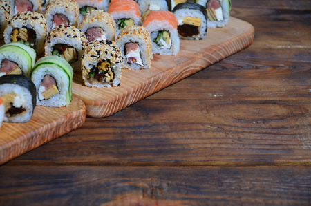 Sushi set of a number of rolls is located on a wooden cutting board on a table in the kitchen of a sushi bar. A traditional dish of oriental cuisine 版權商用圖片 - 90789673