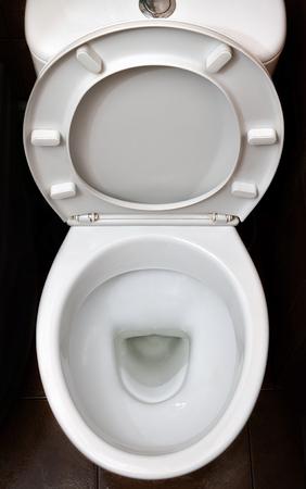Een foto van een witte keramische wc-pot in de kleedkamer of badkamer. Keramisch sanitair voor correctie van de behoefte Stockfoto