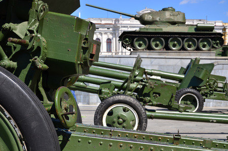Photo of three guns of the Soviet Union of the Second World War against the background of the green tank T-34 Editorial