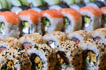 A macro shot of a sushi set of many rolls is located on a wooden cutting board on a table in the kitchen of a sushi bar. A traditional dish of Japanese cuisine Stock Photo