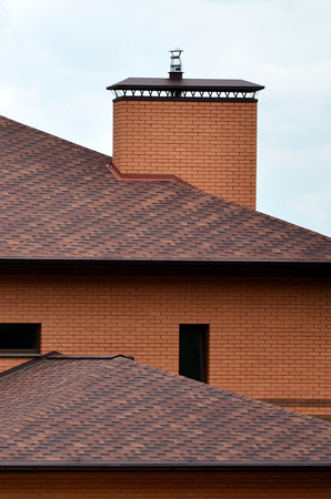The house is equipped with high-quality roofing of shingles (bitumen tiles). A good example of perfect roofing. The roof is reliably protected from adverse weather conditions Editorial
