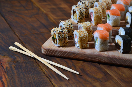 A detailed shot of a set of Japanese sushi rolls and a device for their use (chopsticks), which are located on a wooden cutting board on a table in the kitchen of a sushi bar Stock Photo