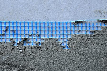 The texture of the wall, covered with gray foam polystyrene plates, covered with a blue reinforcing mesh and covered with a mixture for gluing it. Stage of wall insulation