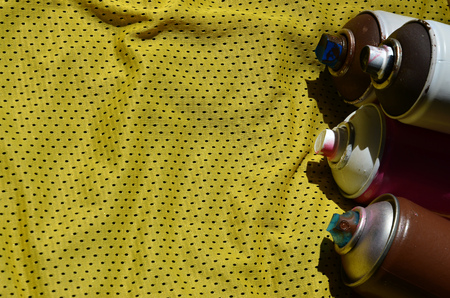 Several used aerosol paint sprayers lie on the sports shirt of a basketball player made of polyester fabric. The concept of youth street art, active sports and eventful lifestyle