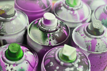 A lot of used spray cans of paint close-up. Dirty and smeared cans for drawing graffiti. The concept of a sweeping and careless drawing of paint. Creative art image