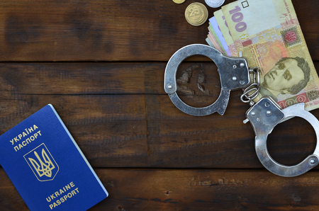 A photograph of a Ukrainian foreign passport, a certain amount of Ukrainian money and police handcuffs. Concept of illegal earnings of Ukrainian citizens abroad